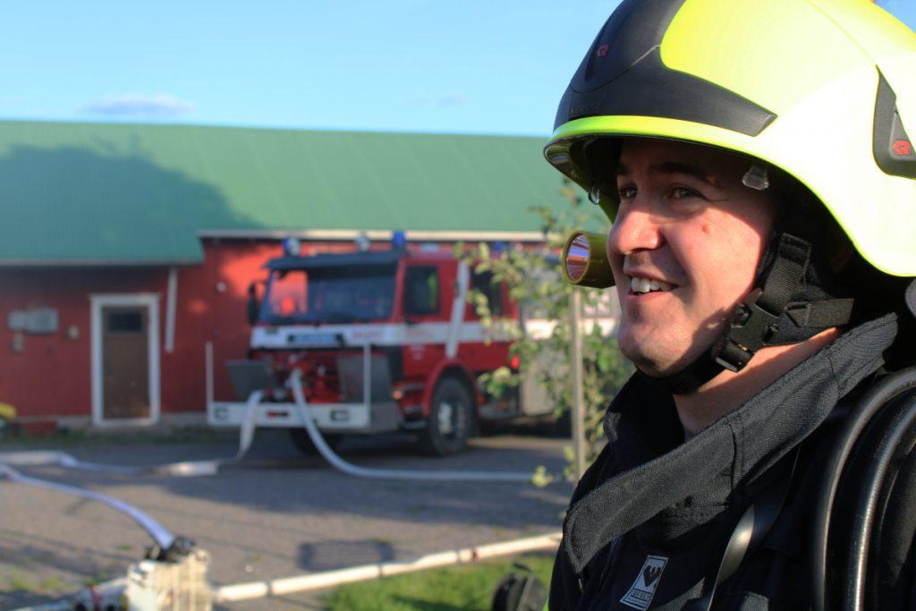 Nuori palomies hymyilee täydessä varustuksessaan, taustalla paloauto