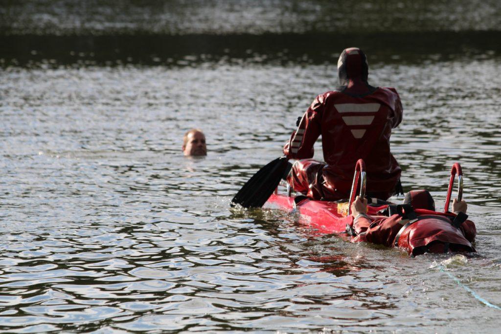 Tuiskulan VPK:n palomies lähestyy märkäpuvusssa ja lautalla meloen veden varaan joutunutta henkilöä harjoitustilanteessa