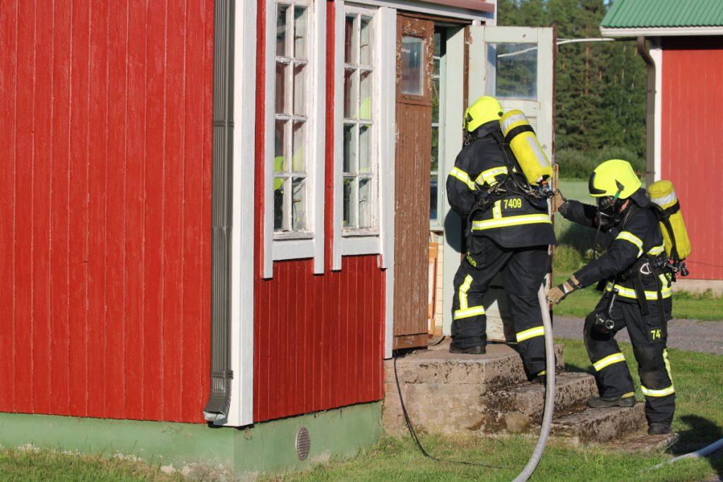 Tuiskulan VPK:n harjoitustilanne, jossa kaksi savusukeltajaa menee punaisen puutalon etuovesta sisään