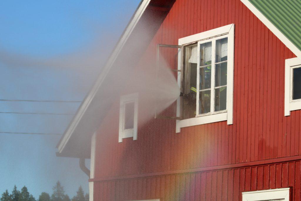 Tuiskulan VPK:n savusukeltajat tuulettavat vesisuihkun avulla punaisen talon vinttikerroksen ikkunasta savua uloa