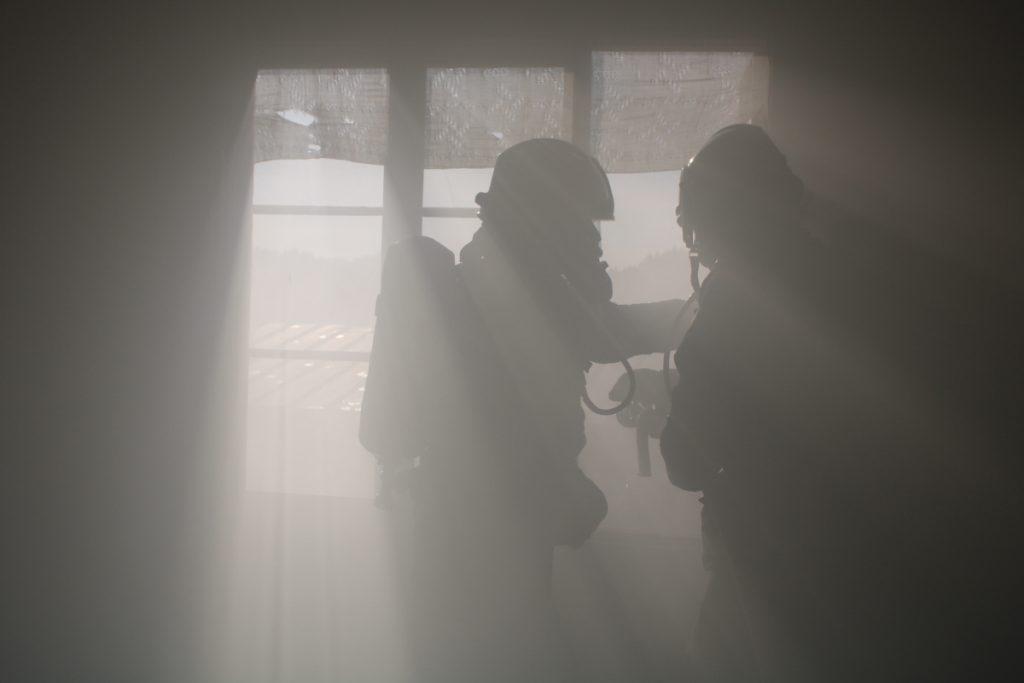 Kaksi savusukeltajaa harjoitustilanteessa suorittavat savunpoistoa rakennuksen sisältä
