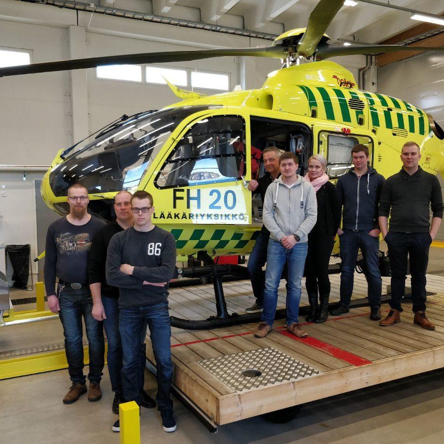 Tuiskulan VPK:n ensivasta osaston henkilöitä yhteiskuvassa helikopterin kanssa