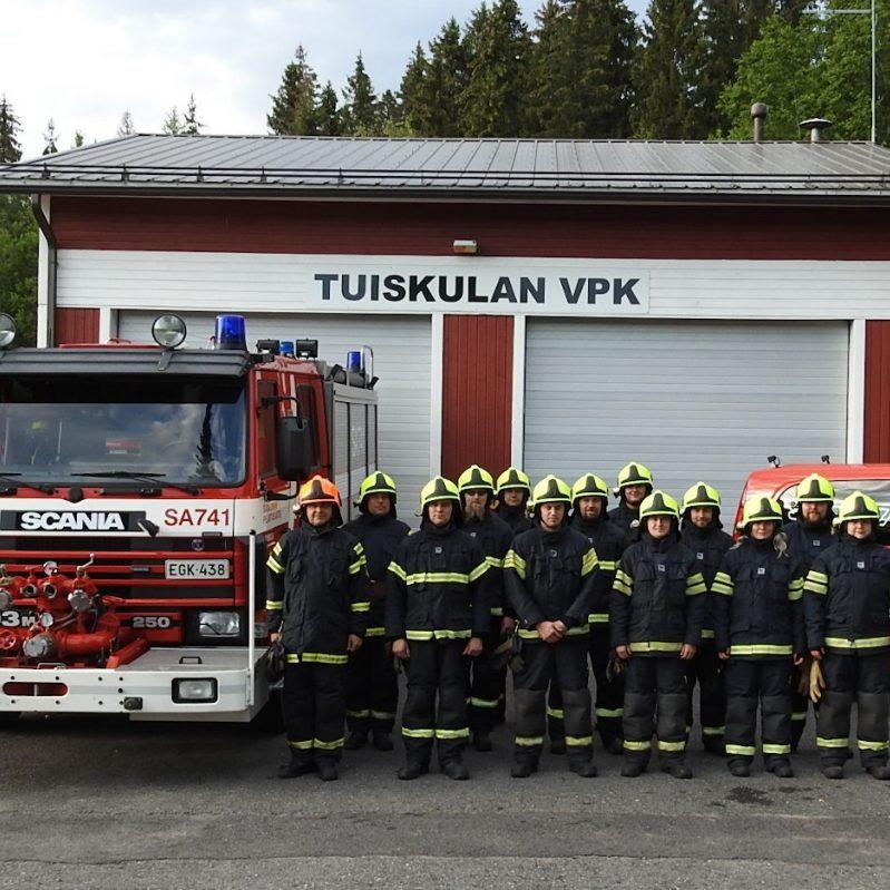 Tuiskulan VPK:n miehistöä yhteiskuvassa paloaseman edessä täydessä varustuksessaan. Kuvassa myös Paloauto.