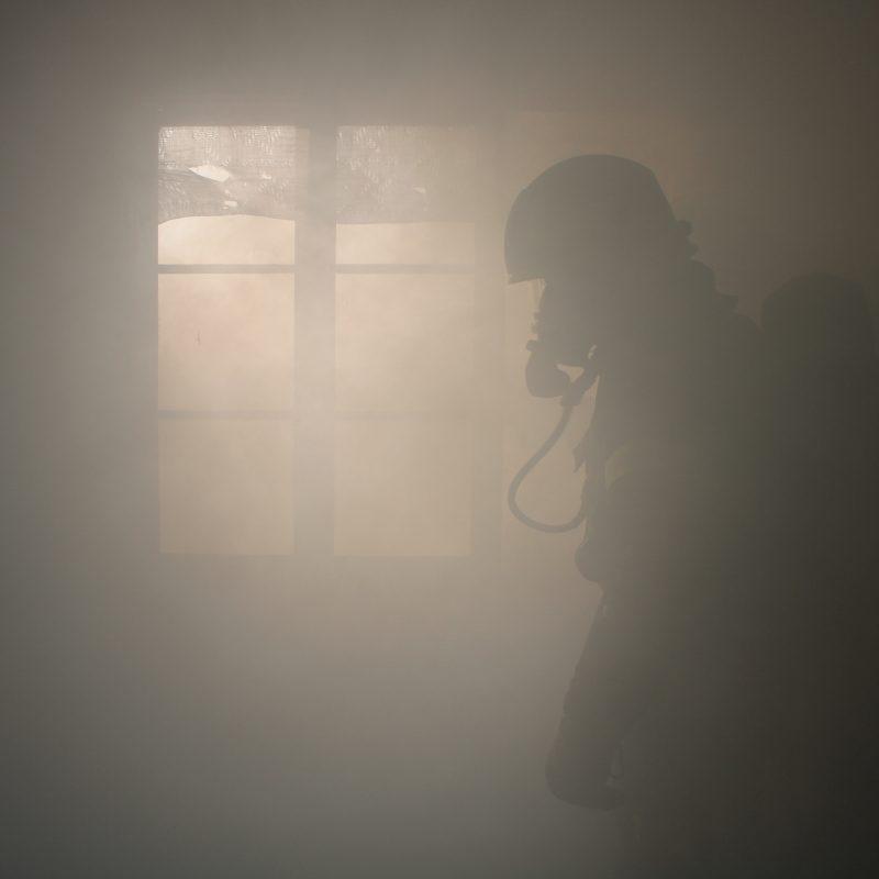 Silhuettikuva Tuiskulan VPK:n savusukeltajasta savun keskellä, taustalla ikkuna